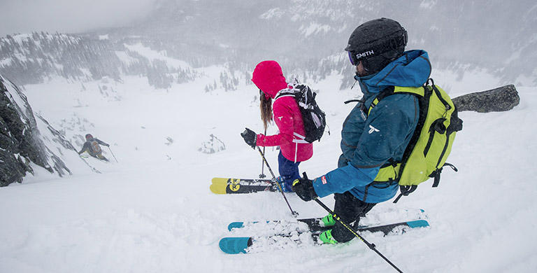 Two skiers getting ready to make a run.