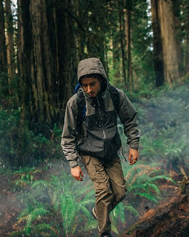 A man hiking in a forest wearing Columbia gear.