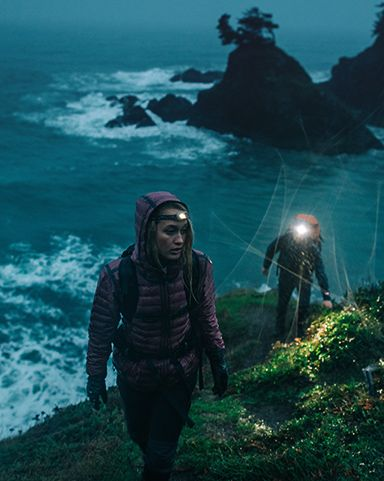 A woman and man hiking by the ocean in Columbia gear.