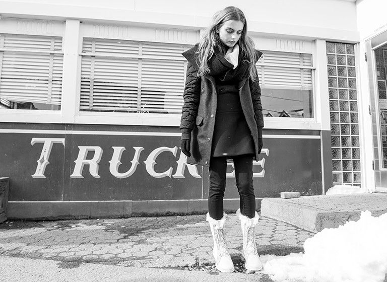 Image of a girl standing outside a building in the snow