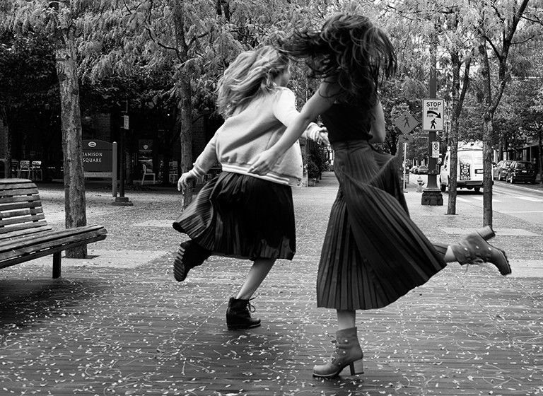 Image of a two girls running down a city street