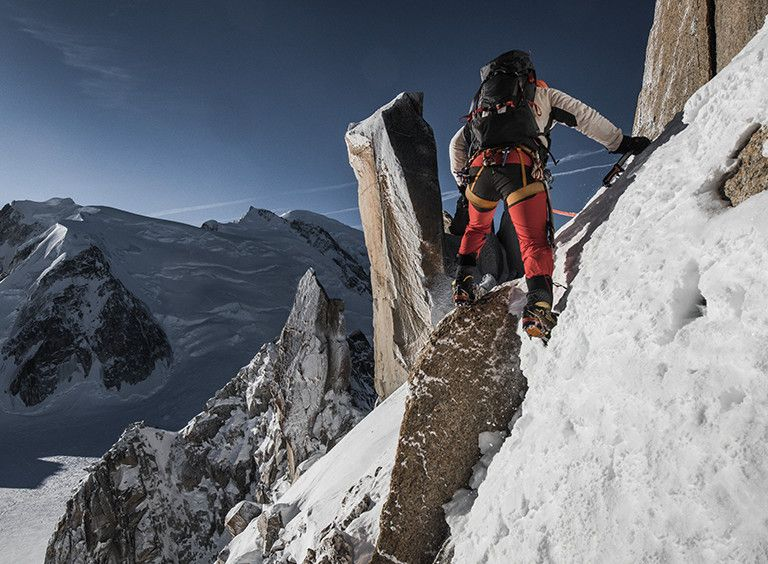 Man alpine climbing on side of mountain.