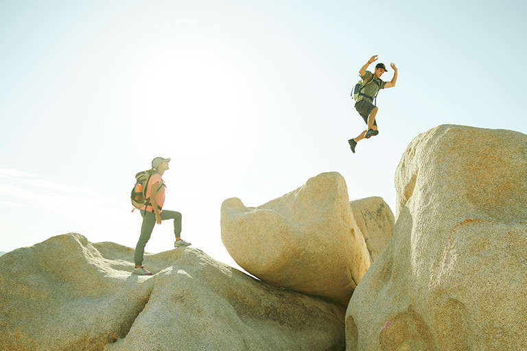 A man and woman hiking on boulders, the man jumping in the air.