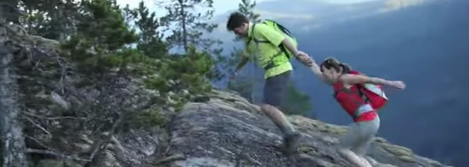 A man and woman holding hands scaling a steep hill, video prompt.