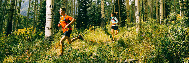 A man and woman trail running in the woods