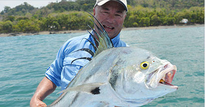 Bob Izumi  holds up a catch while wearing Columbia Performance Fishing Gear.