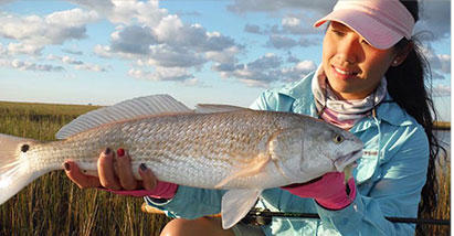 Cindy Nguyen holds up a catch while wearing Columbia Performance Fishing Gear.