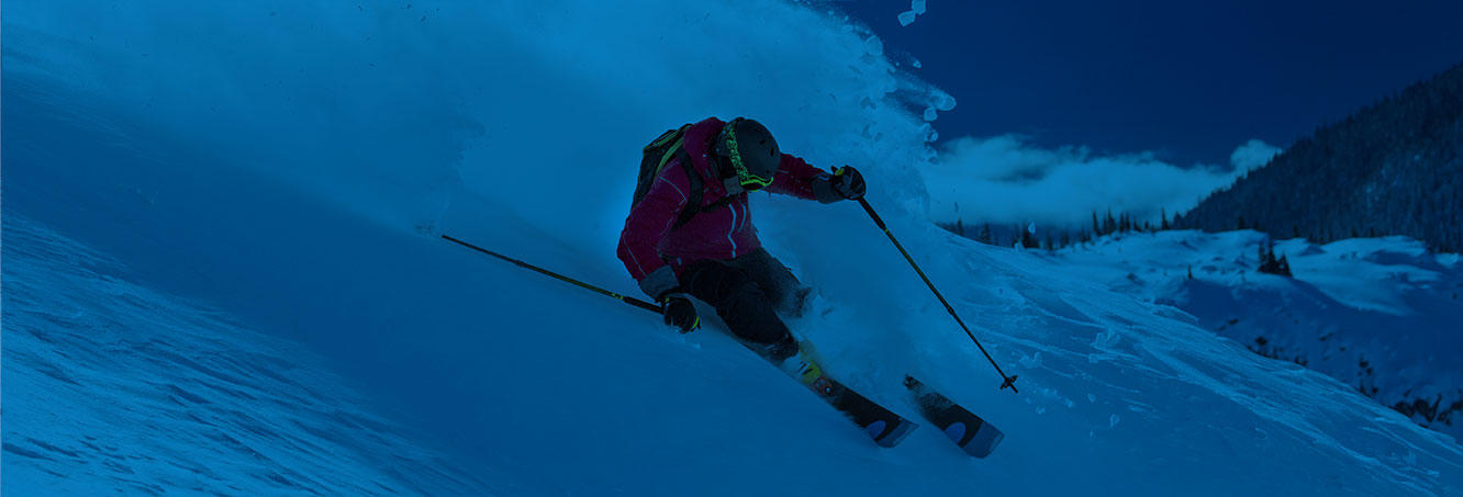 A skier descends a snowy slope on a blue background.