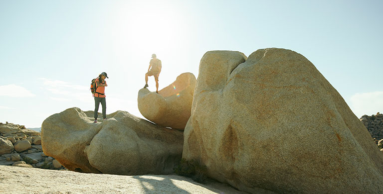 Two hikers standing on boulders.