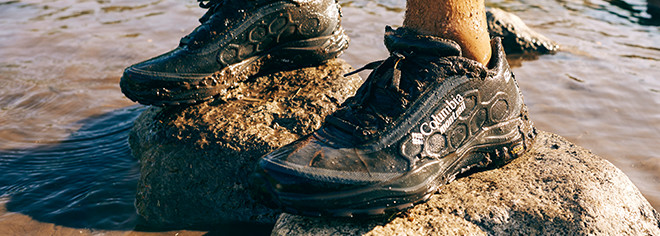 Close-up of a pair of mud-spattered black Columbia Montrail Trient OutDry trail running shoes.