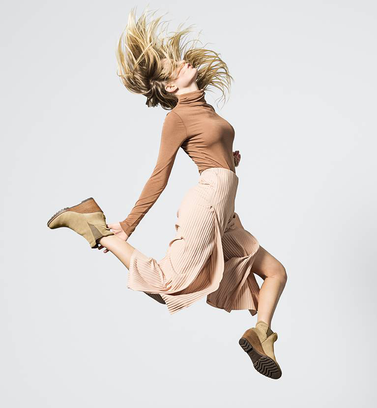 Woman jumping in wedge boots.