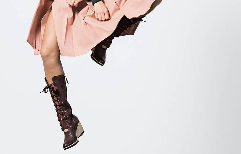Woman jumping in lace-up knee-hi boots.