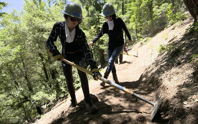 Two young female volunteers work with shovels to widen the Pacific Crest Trail.