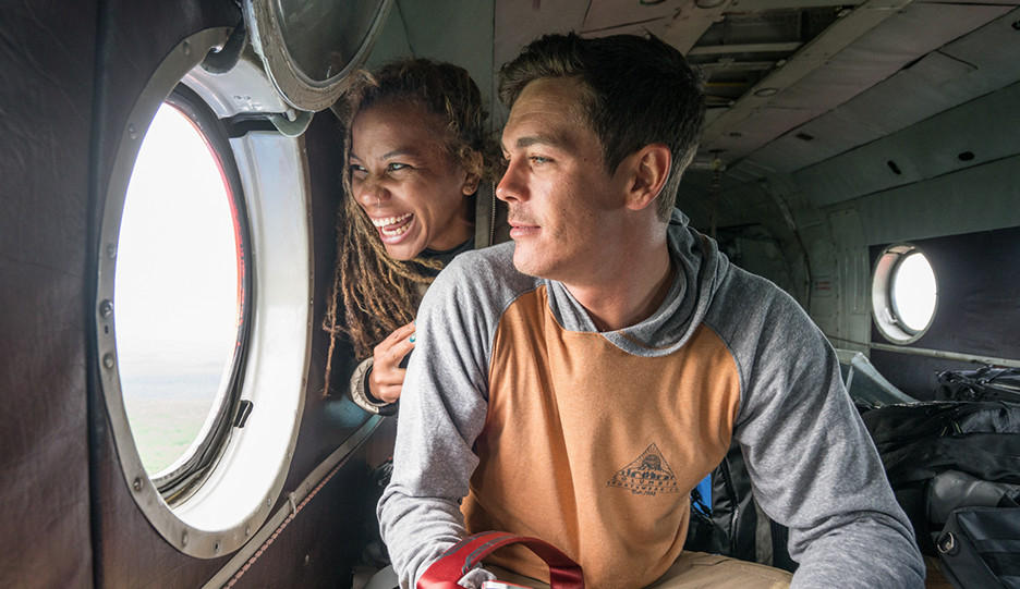 Close-up of Faith and Mark smiling as they look out the window of a helicopter flying above the Kamchatka Peninsula.