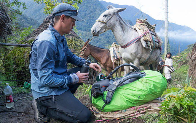 Mark packs up his gear in the Kogi village beside two donkeys.