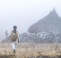 A Kogi villager walks near a hut.