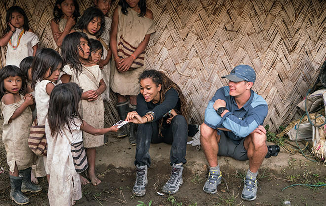 Mark and Faith sit beside a hut and visit with Kogi children.