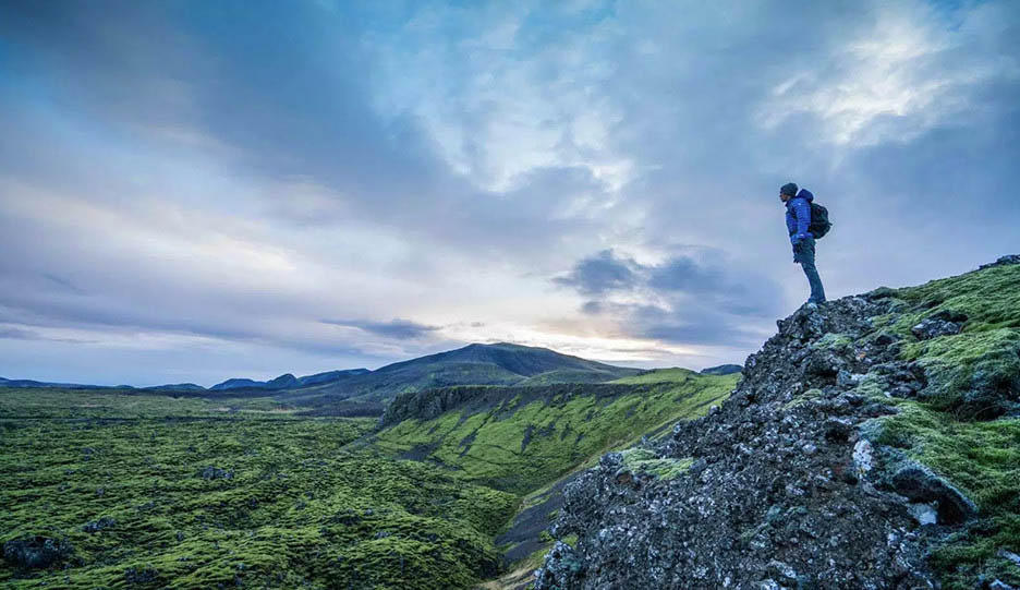 Mark stands on a ridge overlooking rocky landscape; Video on The Give Back in Iceland.