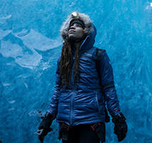 Faith looks up at the ceiling of an ice cave.