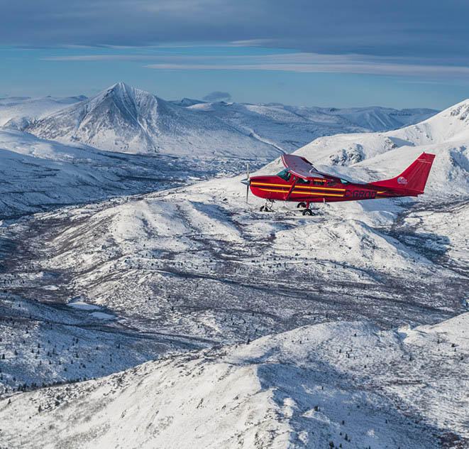 A bush plane carrying Mark and Faith flies over the snowy Yukon wilderness.