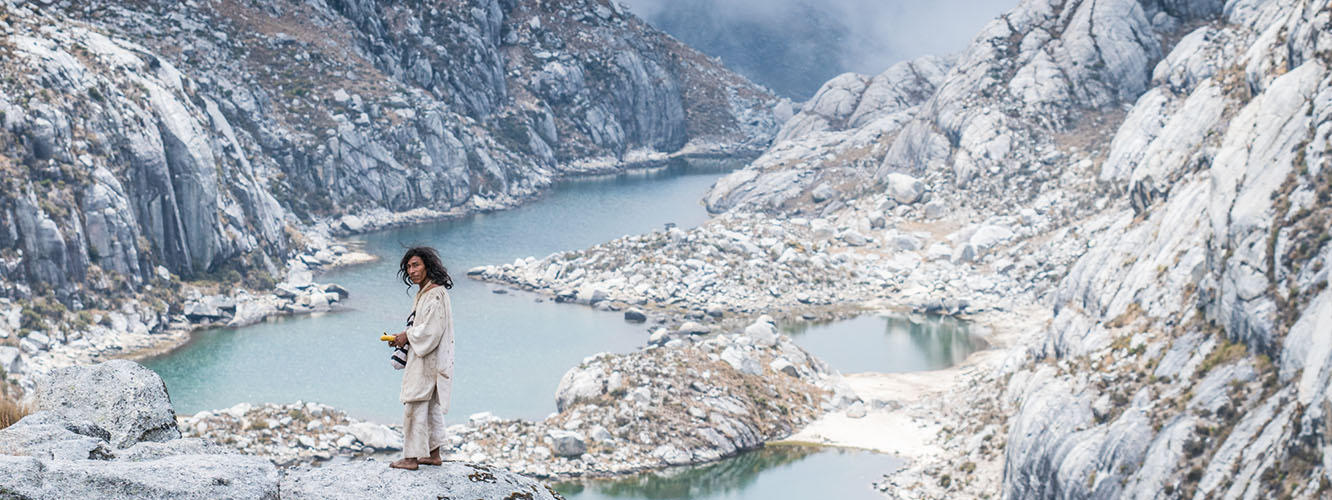 A Kogi man stands on a rock overlooking the sacred lakes.