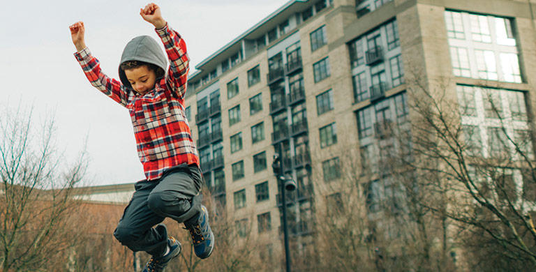 A young boy in outdoor casual wear jumps in the air in a city park.