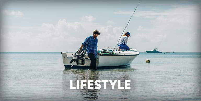 A man and woman fish from a boat in shallow water while wearing casual PFG lifestyle gear.