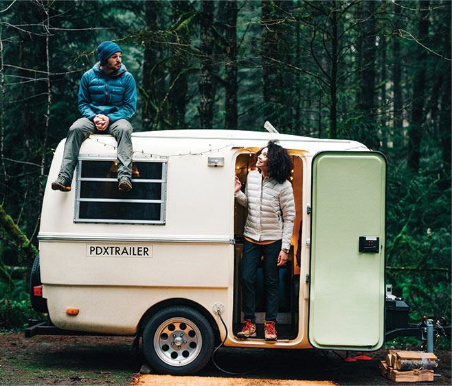 A man and woman wearing RDS-certified down jackets sit and stand beside a camping trailer in the forest.