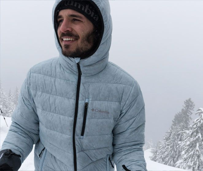 A smiling man stands in the snowy wilderness wearing an RDS-certified down jacket.