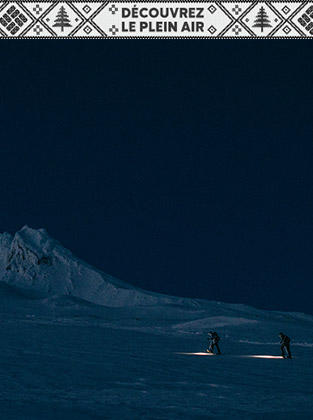 Skiers on a snowy mountain at night.
