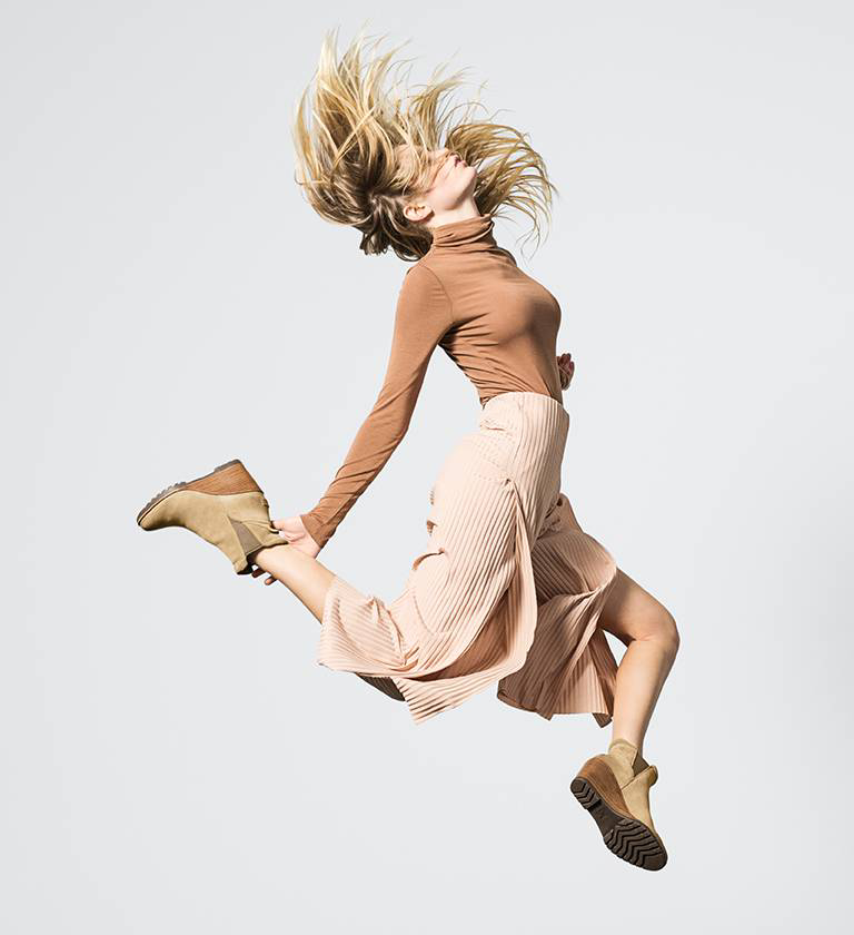 A woman jumping in Chelsea Wedge boots.
