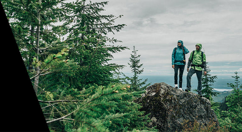 A woman and man in Titanium gear stand atop a rock in a forested mountain setting.