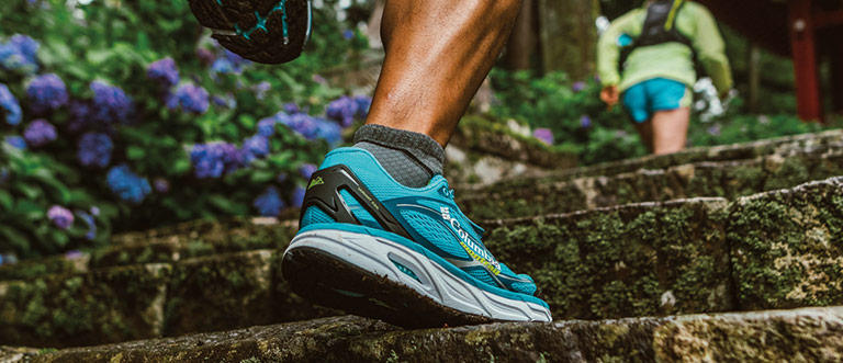 Image of a man's leg an foot wearing running shoes in the woods.