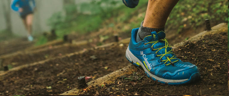 Image of a foot wearing running shoes in the forest.