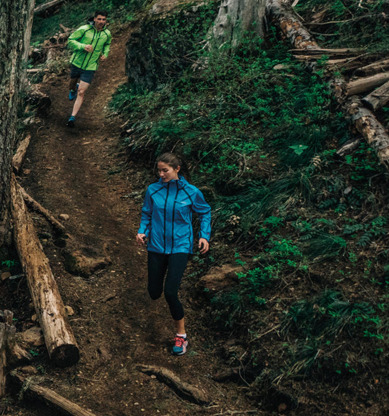 A woman and a man trail running in a forest.