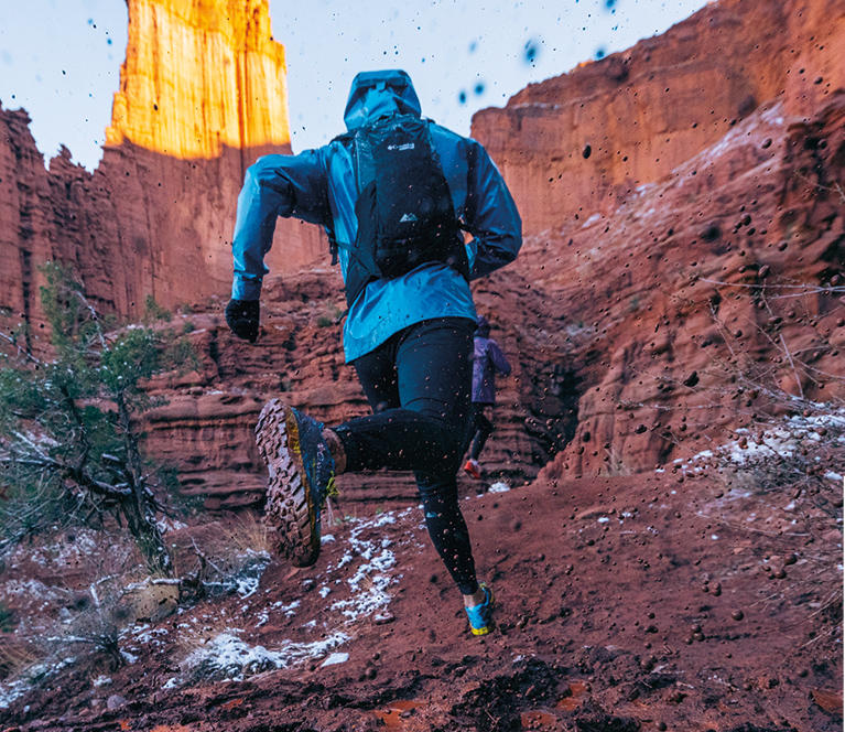 A hip-down image of a man running in a canyon.