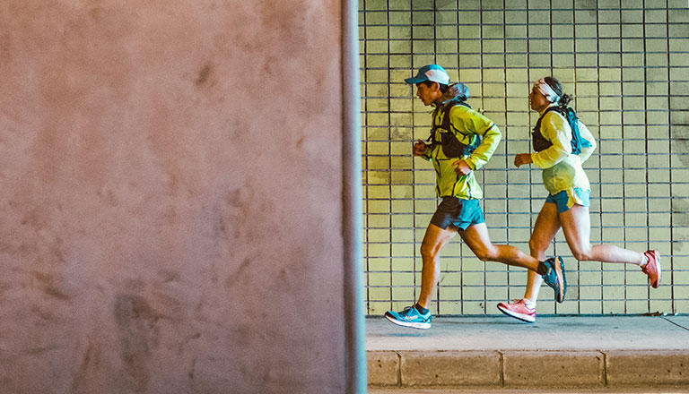 Ruy Ueda and Sandrine Christin run on a Tokyo sidewalk while wearing Columbia Montrail gear.