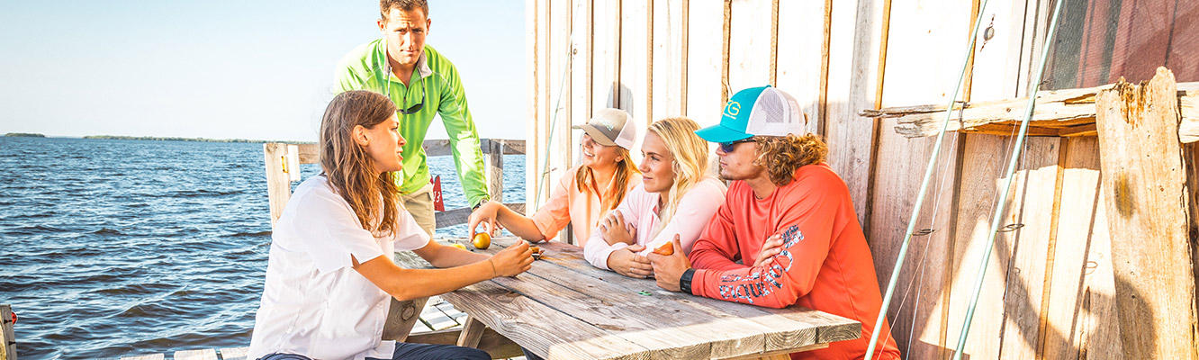 A group of people in PFG gear sit around a dockside picnic table.