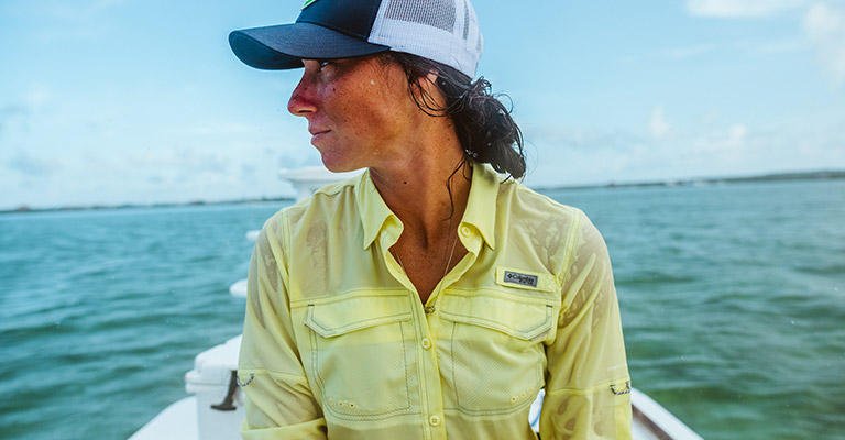 A woman in PFG gear in a boat on a sunny day.