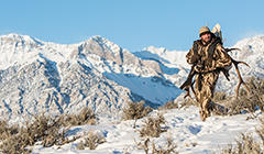 A man in camouflage Columbia hunting gear stands atop a snowy hillside.