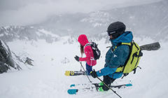 A man and woman in Columbia ski gear peer down a snowy slope.