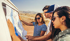 A group of people in Columbia gear gather around a travel map in a desert setting.
