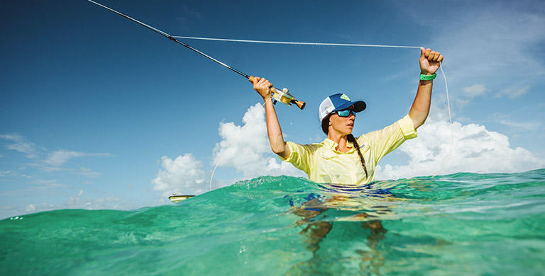 A woman in waist-deep water fishing in the sea.