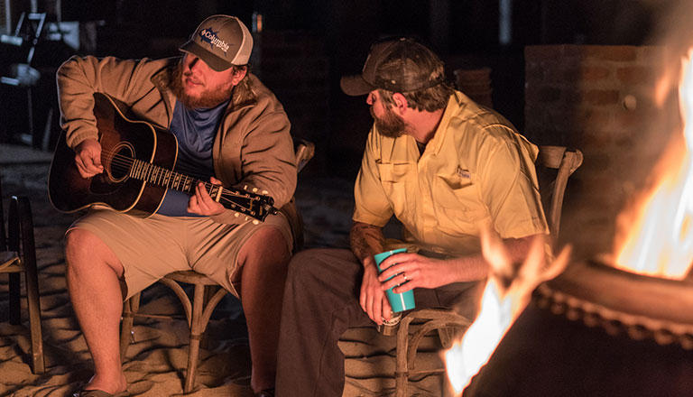 Country star Luke Combs plays guitar by a campfire.