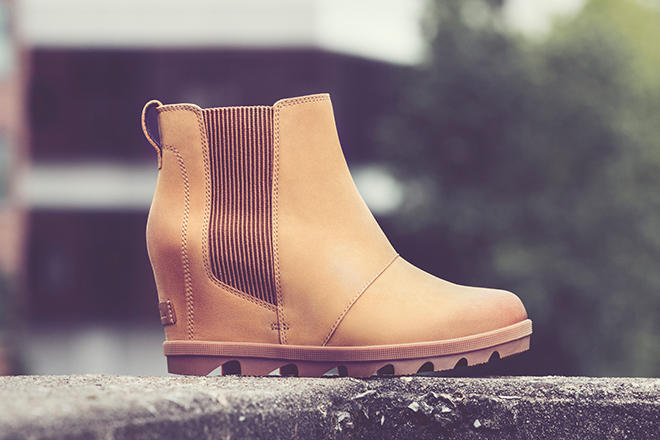 Close-up shot of a camel-brown Joan Wedge Chelsea boot in an urban setting