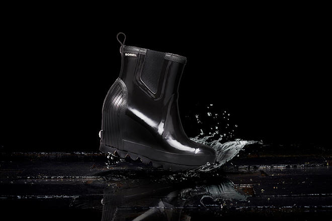 Image of a pair of Joan Rain Wedge Chelsea boots splashing in rain on a black background
