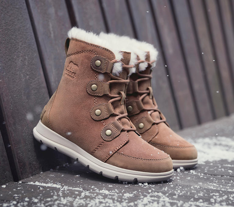 a0bd4235aad21 Left  A woman in a winter urban setting at night wearing the Explorer Joan  boot