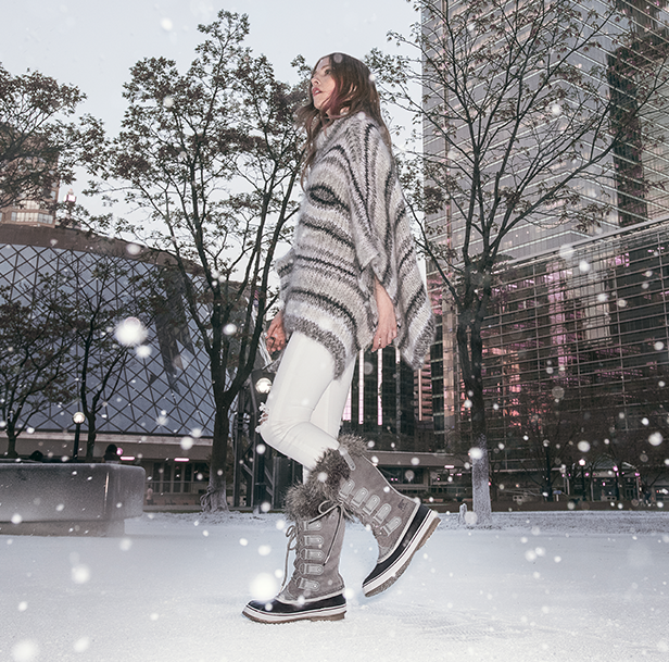 Woman walking in snow city wearing Joan of Arctic boots