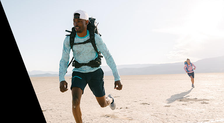 Two trail runners in Columbia Titanium gear jogging through the desert.