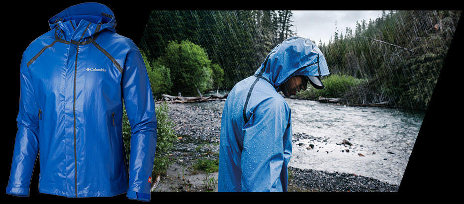 A person in an OutDry™ Extreme jacket hiking a riverbank.
